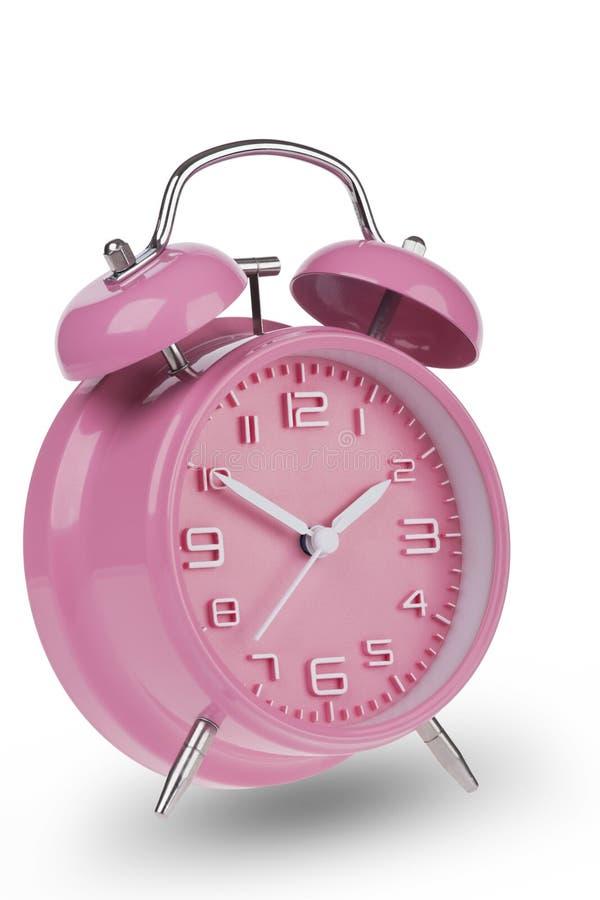 桃红色闹钟用在10和2的手 库存照片