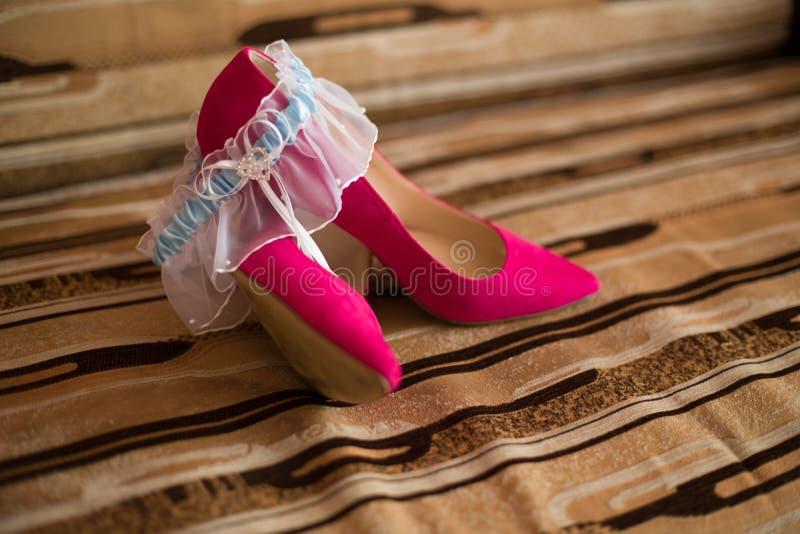 桃红色鞋子和婚礼袜带 免版税库存图片