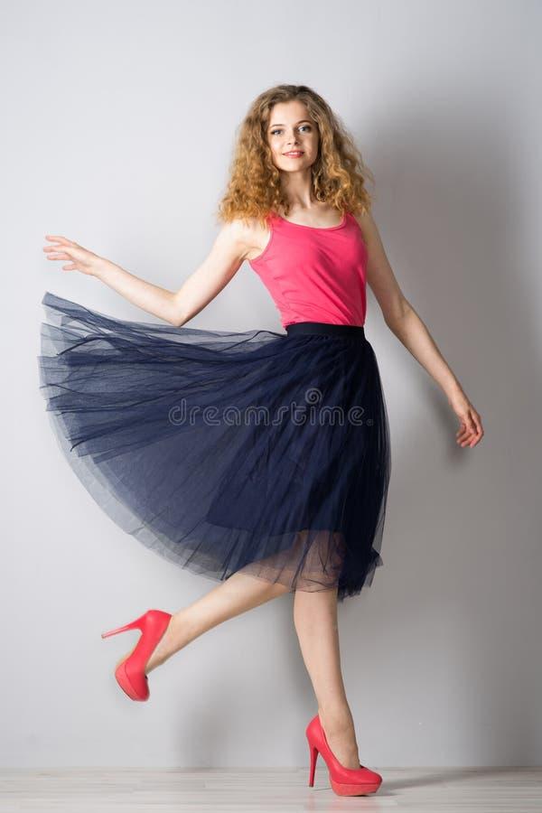 桃红色鞋子的年轻美丽的妇女 免版税库存照片