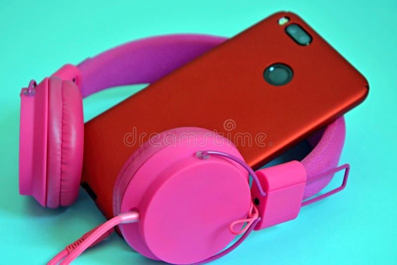 桃红色顶上的外在大耳机和一个电话有一台双重照相机的在红色防护盒 在蓝色背景的特写镜头 免版税库存照片