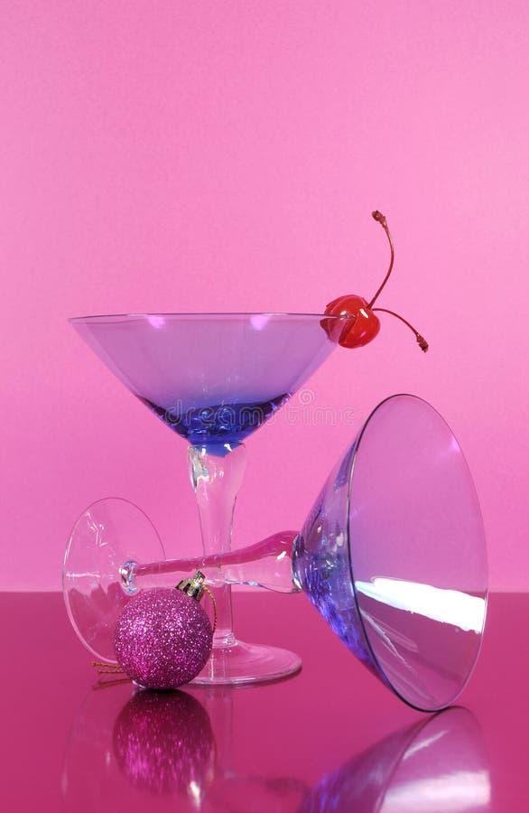 桃红色题材新年快乐党与葡萄酒蓝色马蒂尼鸡尾酒鸡尾酒杯和除夕装饰 免版税库存图片