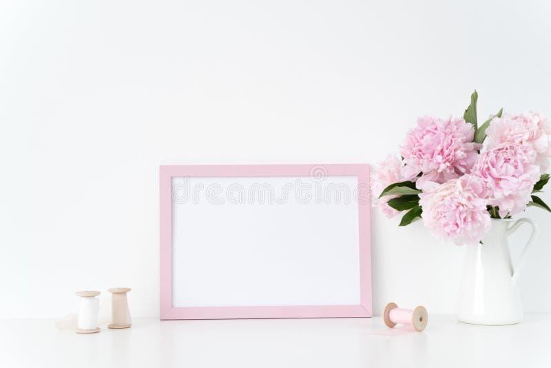 桃红色风景框架嘲笑与桃红色牡丹和丝绸丝带在框架旁边,躺在了您的行情、促进、标题或者de 免版税库存照片