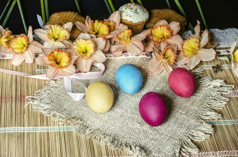 桃红色黄水仙和饼干在粗麻布用被绘的复活节彩蛋在秸杆地毯说谎 免版税库存图片