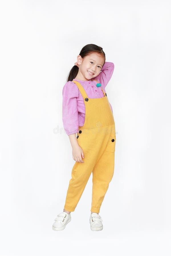 桃红色黄色粗蓝布工装姿势的微笑的小亚裔孩子女孩在白色背景接触头发保持被隔绝 ??  免版税库存图片