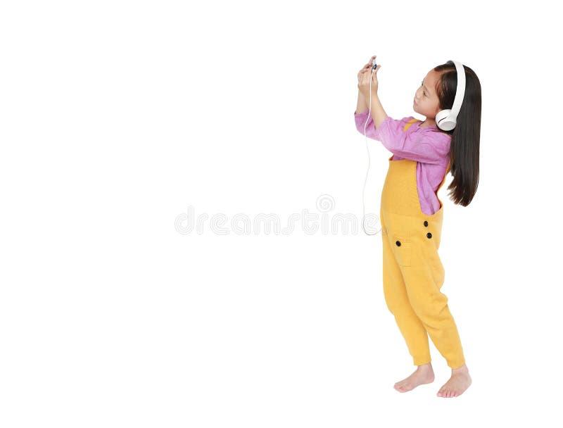 桃红色黄色粗蓝布工装的可爱的矮小的亚裔儿童女孩有耳机的对由被隔绝的智能手机享受听的音乐  免版税图库摄影