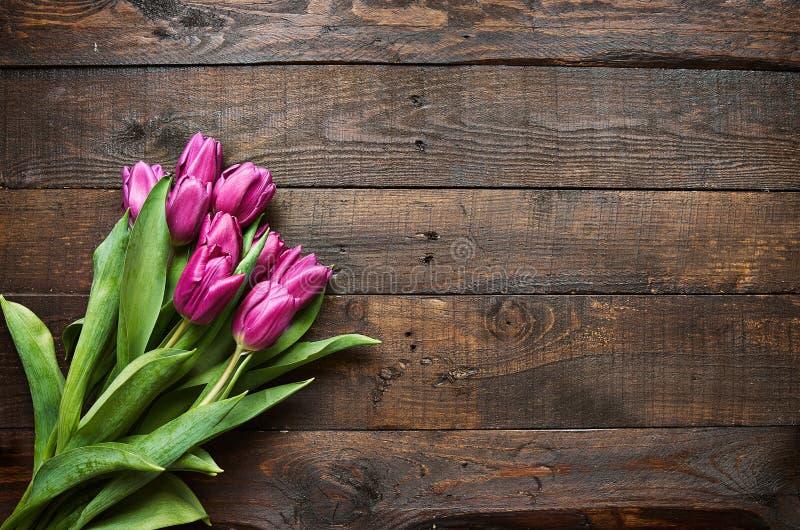 桃红色,在黑暗的谷仓木板条背景的郁金香束 免版税库存图片