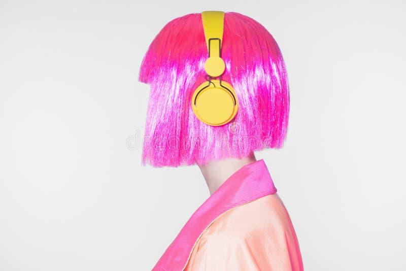 桃红色头发妇女听的音乐 免版税库存照片