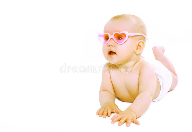 桃红色玻璃的凉快的逗人喜爱的婴孩 免版税库存照片