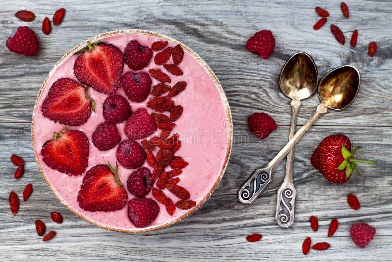 桃红色acai, maca粉末圆滑的人碗冠上了用切的草莓、莓和goji莓果 免版税库存图片