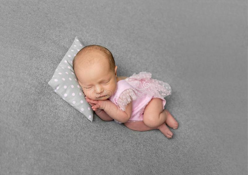 桃红色drees睡觉的可爱的新出生的女孩 免版税库存图片