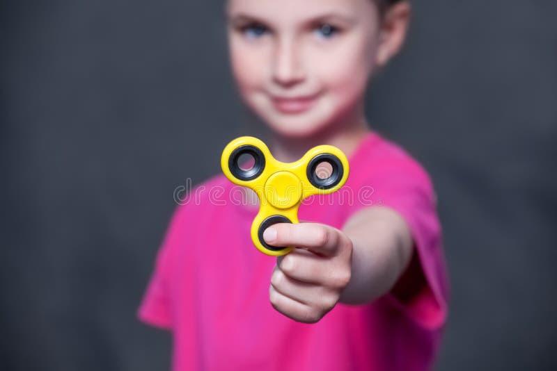 桃红色T恤杉的小美丽的女孩在手中扮演黄色锭床工人 免版税库存图片