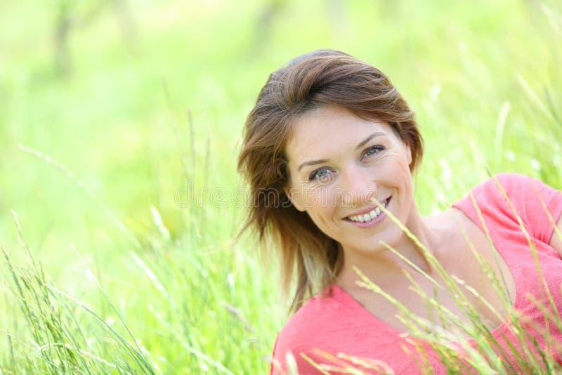 桃红色T恤杉的微笑的美丽的妇女在草 免版税库存照片