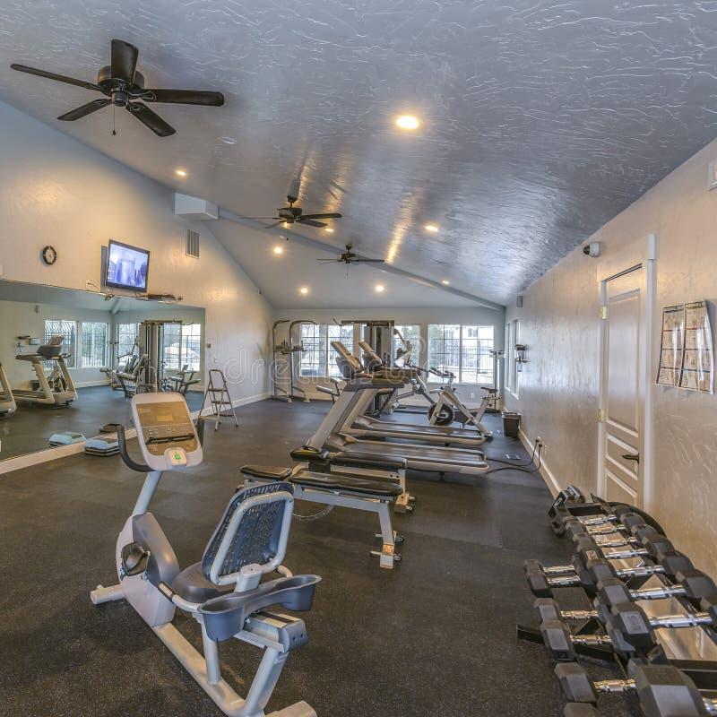 框架一间宽敞健身健身房的正方形内部与各种各样的运动器材的 免版税库存照片