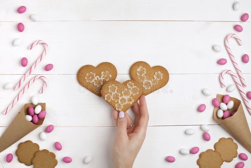 框架五颜六色的糖果、镶边棒棒糖和曲奇饼以心脏的形式在手中 顶视图,白色木背景 免版税库存照片