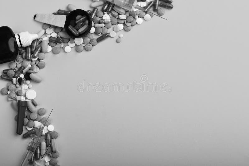 框架在一边上和胶囊做成把放的由药片 医疗抽象概念 药物临近糖浆瓶,注射器和 免版税库存图片
