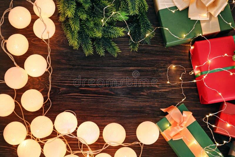 框架由圣诞礼物和彩色小灯做成在木背景 库存图片