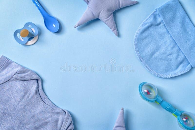 框架由婴孩衣裳和辅助部件制成在颜色背景,平的位置 免版税图库摄影