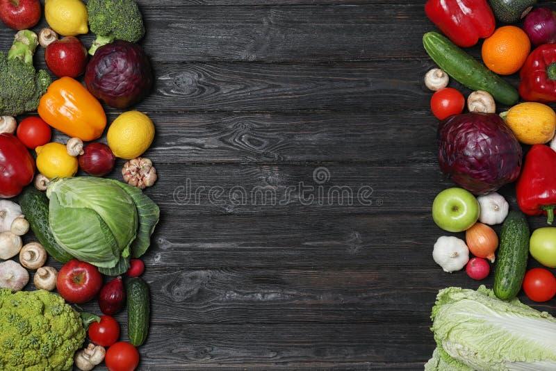 框架由成熟水果和蔬菜做成在黑木背景,平的位置 免版税库存图片
