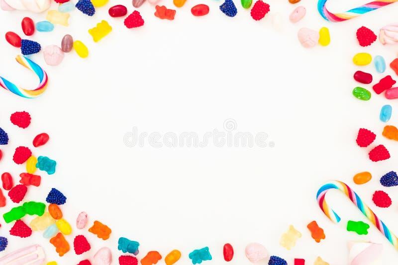 框架由明亮的糖果、橘子果酱和棒棒糖制成在白色背景 平的位置,顶视图 不健康的食物 免版税库存图片