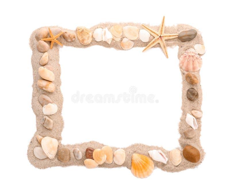 框架由沙子、海小卵石和壳做成在白色背景 免版税图库摄影