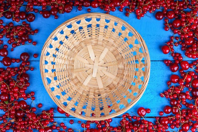 框架由红浆果和樱桃制成与柳条筐 图库摄影