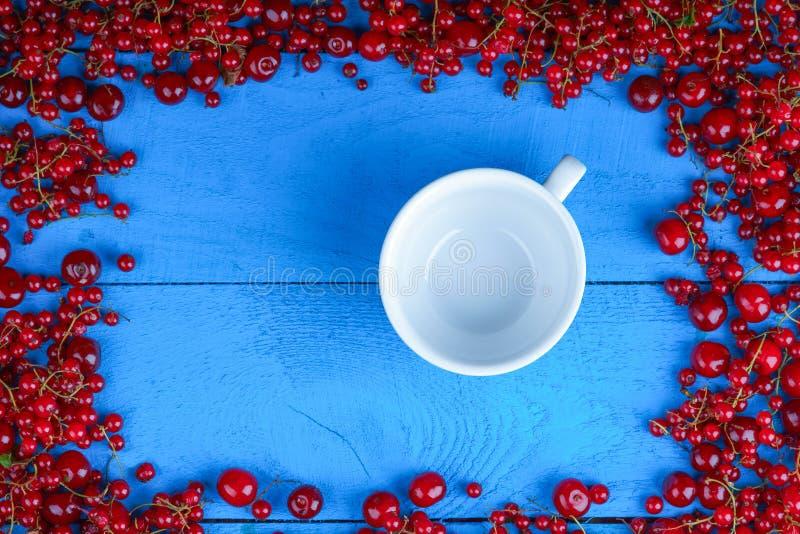 框架由红浆果和樱桃制成与空的咖啡杯 库存图片