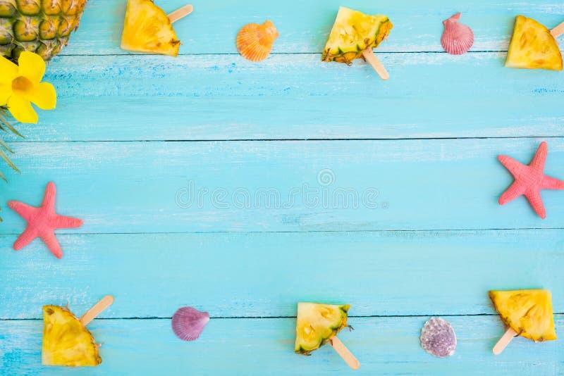 框架由菠萝冰棍儿棍子、海星和壳做成在木板条蓝色颜色 免版税库存图片