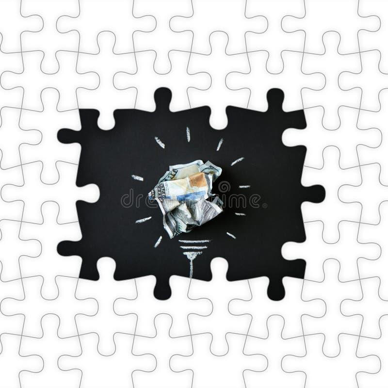框架由难题和构成制成与被弄皱的金钱当电灯泡在黑背景 免版税库存照片