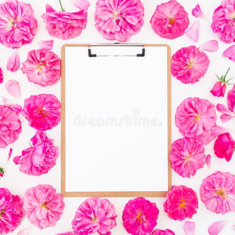框架由紫色玫瑰、毛茛属和剪贴板制成在白色背景 平的位置,顶视图 桃红色花的花卉样式 免版税库存图片