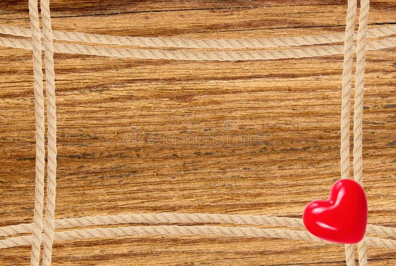 框架组成由绳索和红色心脏在木背景 免版税图库摄影