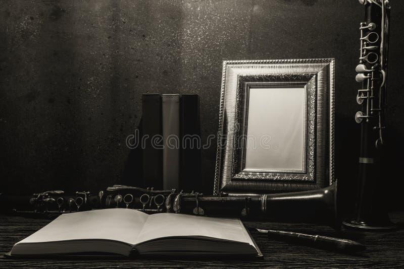 画框静物画在木桌上的与单簧管 库存照片
