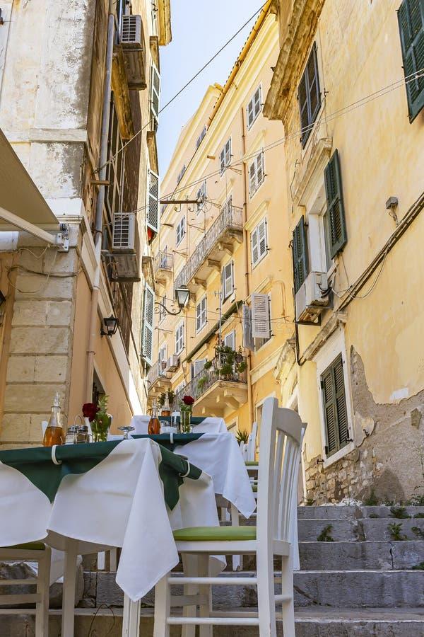 桌准备好科孚岛镇,科孚岛,希腊小街道的客人  免版税库存图片