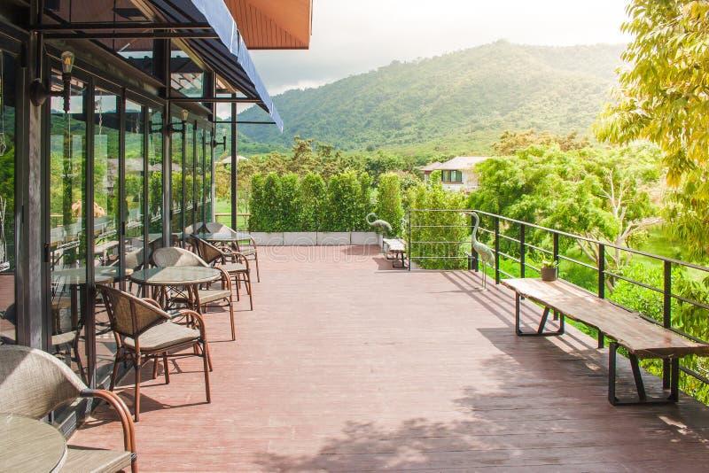 桌和椅子地方行木大阳台的在与美好的风景观点的餐馆或咖啡咖啡馆外面 免版税库存照片