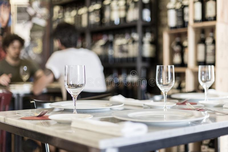 桌在有一位对同性恋者的餐馆设置了在背景中 免版税库存图片