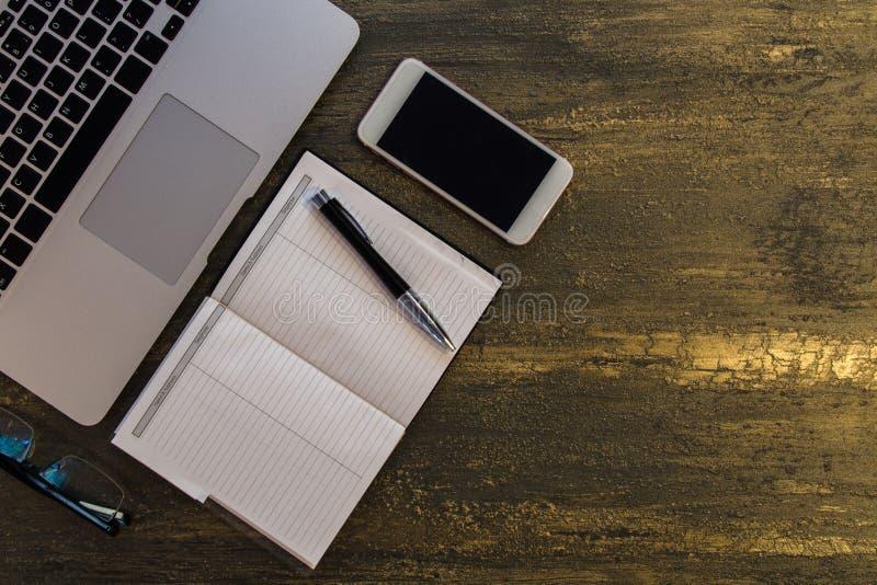 桌或书桌顶视图有膝上型计算机、空白的笔记本、笔和巧妙的电话的在老古铜色背景 免版税库存图片