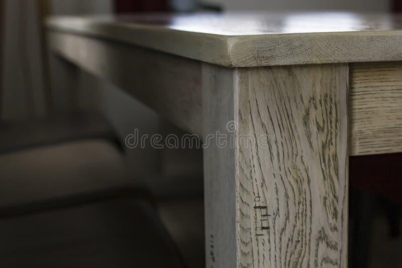 桌的角落的看法与一个木纹理和光滑的工作台面的点燃了从窗口的自然光 图库摄影