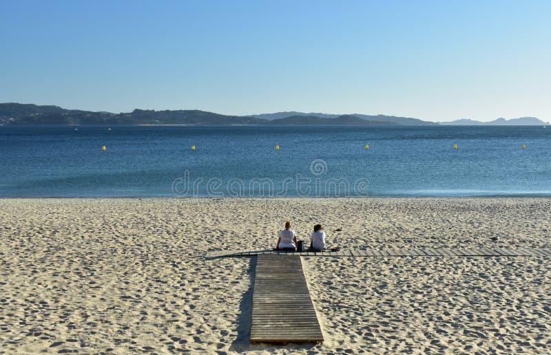 桑克森克索,西班牙 2018年10月 两名妇女是休息和看在海滩木板走道的看法 日落,晴天 图库摄影