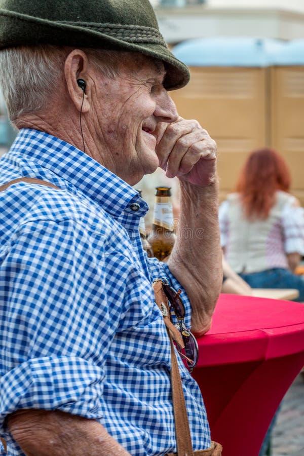 桑福德,佛罗里达- 2016年10月14日-德国节日 传统皮短裤的一个更老的人愉快地笑并且享受音乐费斯特 免版税库存照片
