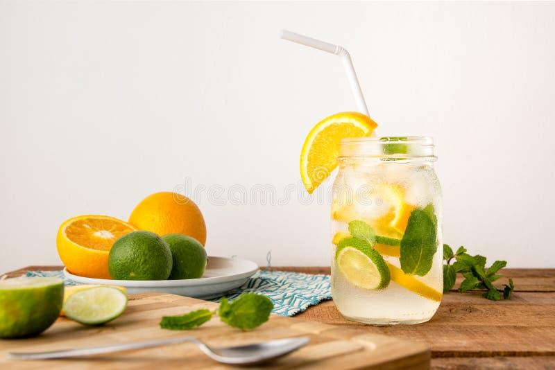 桔子、柠檬和石灰被灌输的水饮料在桌面与拷贝空间文本的 库存图片