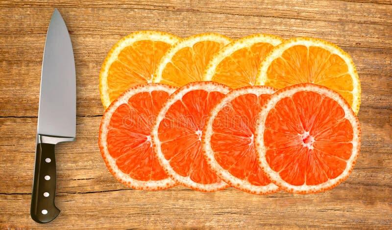 桔子,葡萄柚和刀子在白色隔绝的切板图片