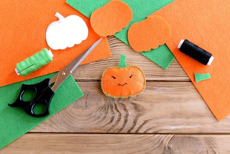 桔子感觉南瓜玩具、剪刀、毛毡平的片断,绿色和黑色穿线,针,在木背景的纸模板 免版税库存照片