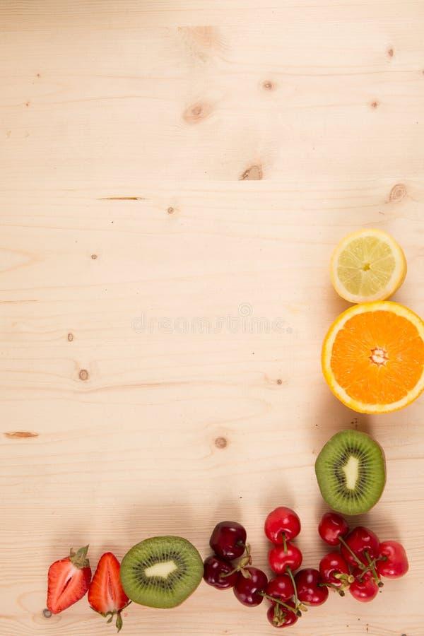 桔子,猕猴桃,樱桃,在木背景的草莓 免版税库存图片