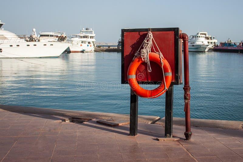 桔子lifebuoy在游艇背景的码头在海附近 在水和抢救的安全从淹没 图库摄影