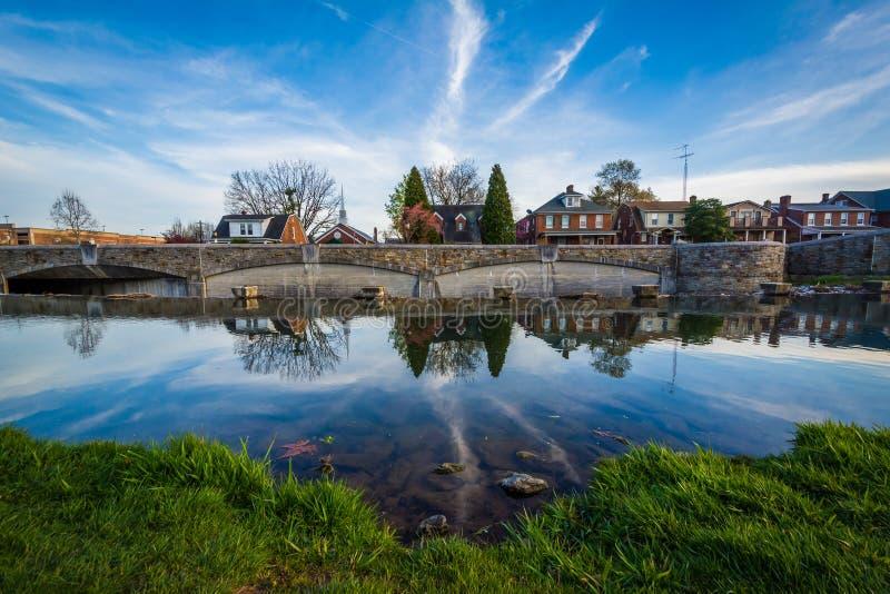 桥梁和房子反射在卡洛尔小河,在弗雷德里克, 3月 库存照片