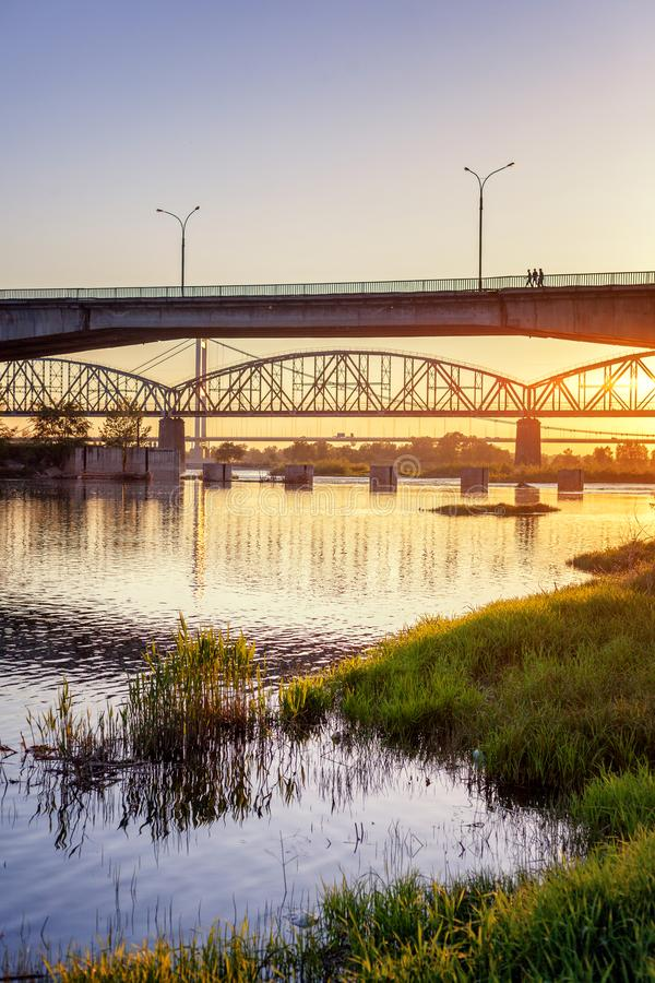 桥梁和河落日的光芒的,美丽的城市 免版税库存照片