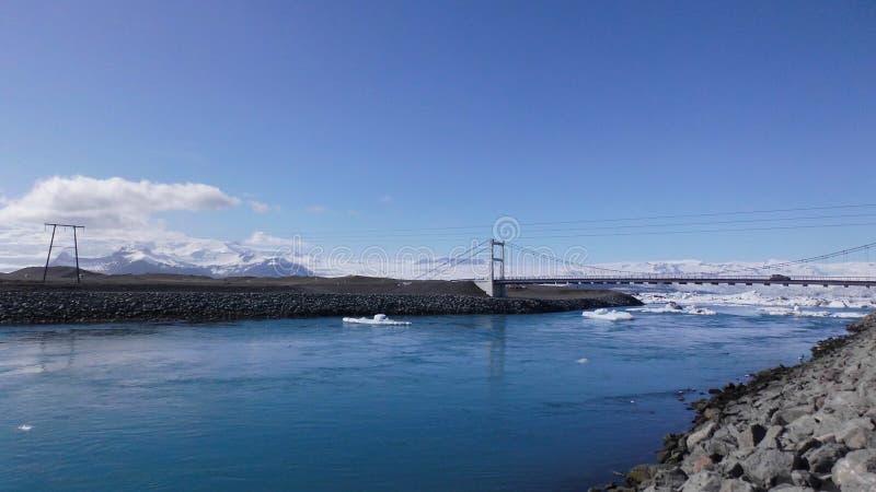 桥梁和浮动蓝色冰山在河 免版税库存照片