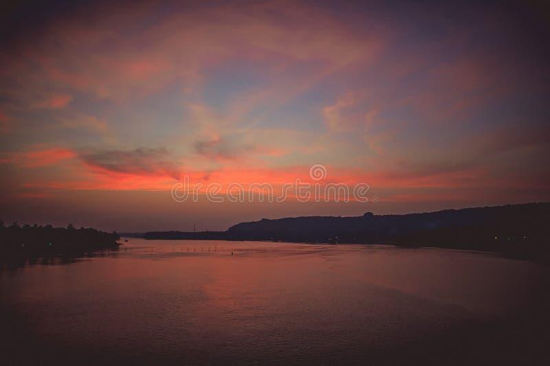 从桥梁的看法在美好的日落的河与有启发性云彩 库存图片