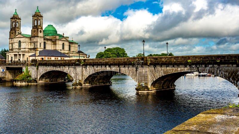 桥梁的美丽的景色在河香农,Ss教区教堂的  彼得和保罗在阿斯龙镇 免版税库存图片