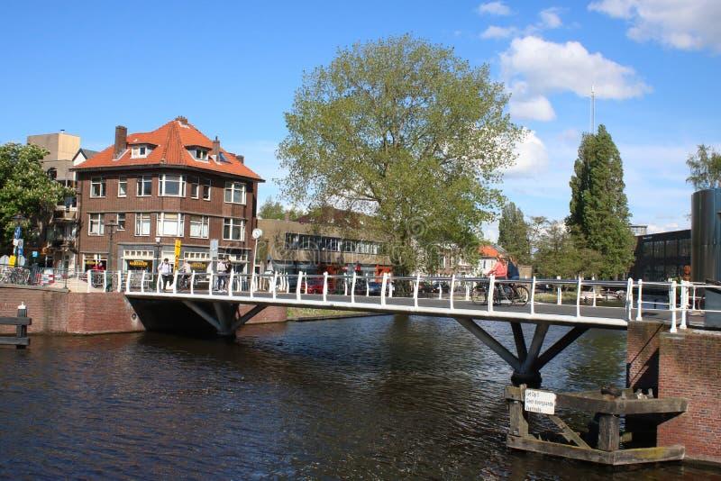 桥梁的骑自行车者在运河在莱顿,荷兰 图库摄影