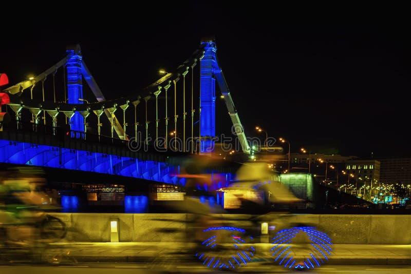桥梁背景的抽象快速的骑自行车者,城市照明,行动迷离 现代生活方式的概念 图库摄影